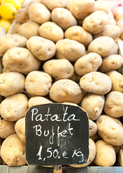 Stock photo: Pile of potatoes on market stall with price.
