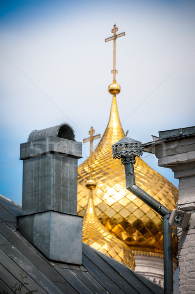 Golden domes with crosses behind old roof. Stock photo © kyolshin