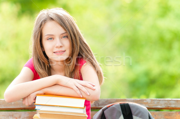 happy student girl sitting on bench with books and smiling Stock photo © kyolshin
