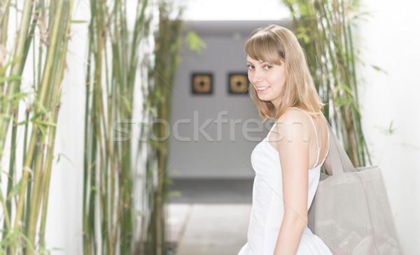 Pretty smiling woman entering hotel hall. Stock photo © kyolshin
