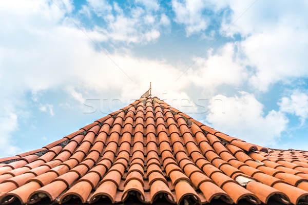 Old tiled roof with sky in background. Stock photo © kyolshin