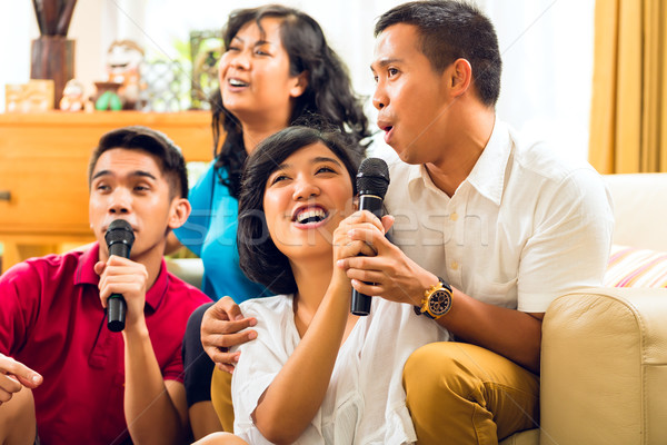 Asian people singing at karaoke party and having fun Stock photo © Kzenon