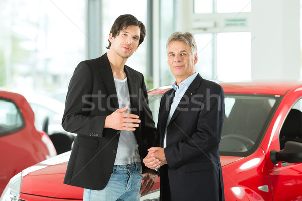 Mature and young man with autos in car dealership Stock photo © Kzenon