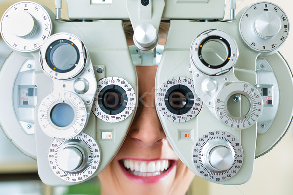 Young woman at phoropter for eye test Stock photo © Kzenon