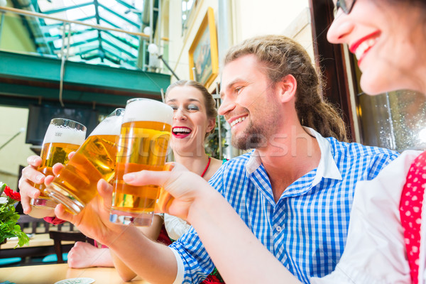 friends drinking beer in Bavarian restaurant or pub Stock photo © Kzenon
