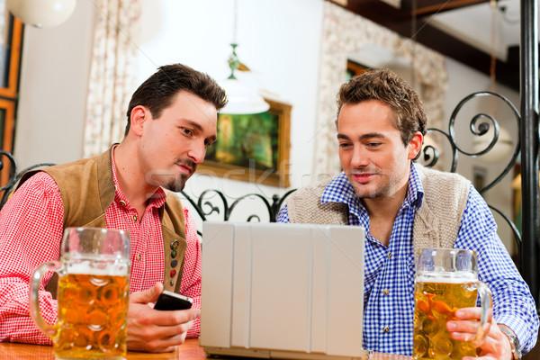 Twee vrienden pub laptop traditioneel kleding Stockfoto © Kzenon