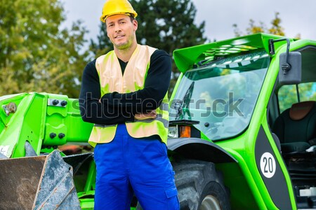 architect in front of excavator using pad or tablet Stock photo © Kzenon