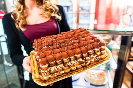 Female baker presenting cake in confectionery Stock photo © Kzenon