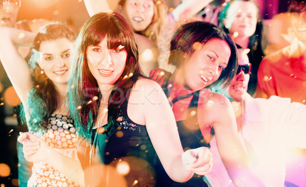 Women and men dancing in club or disco having party Stock photo © Kzenon