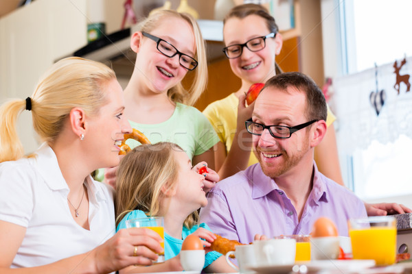 Stock photo: Family in kitchen having breakfast together