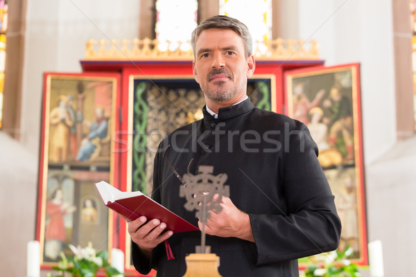 Priest in church with bible in front of altar Stock photo © Kzenon