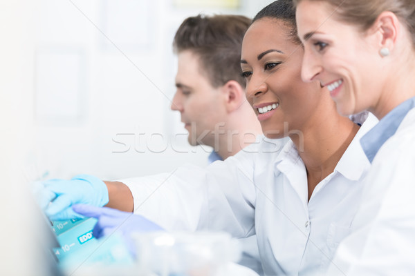 Group of researchers during work on devices in laboratory Stock photo © Kzenon
