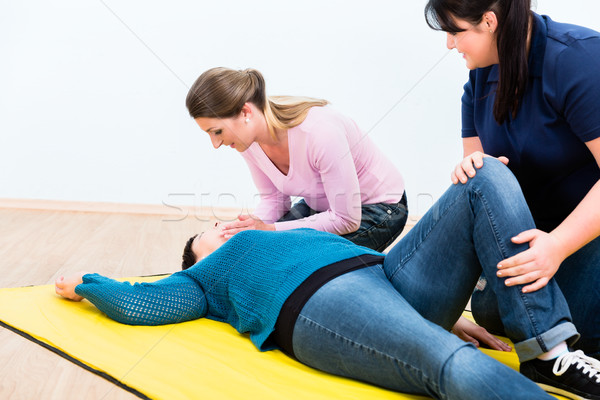 Women in first aid class training to position injured person Stock photo © Kzenon