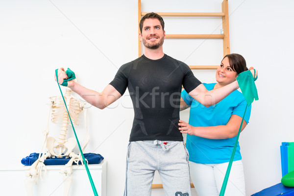 Stock photo: Young man exercising with resistance band in physical therapy