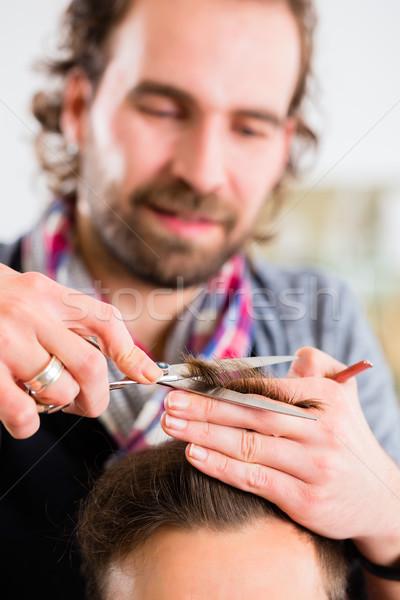 Barber trimming man hair in haircutter shop Stock photo © Kzenon