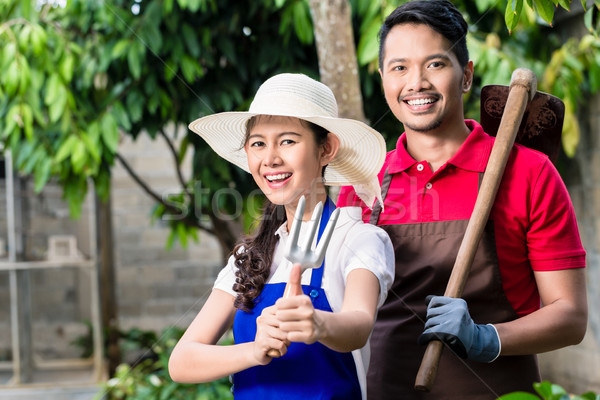 Young Asian couple smiling while working in the garden Stock photo © Kzenon