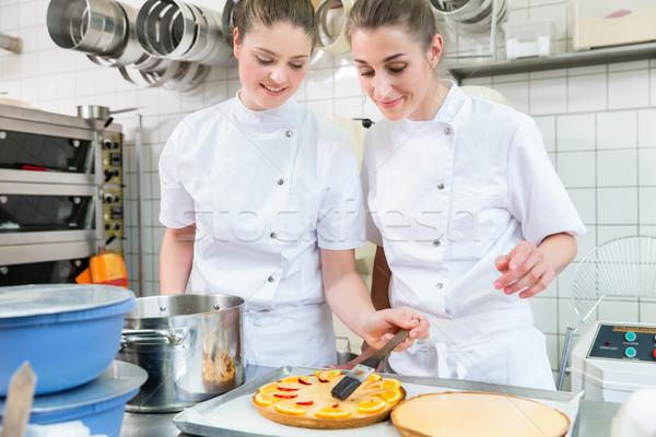 Women putting fruit on cakes in pastry bakery Stock photo © Kzenon