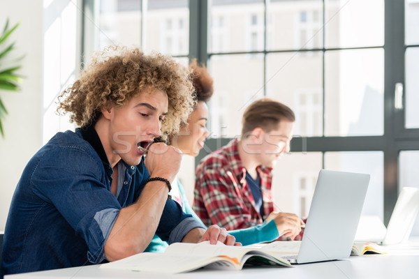Funny student yawning in front of a book while sitting down at desk Stock photo © Kzenon