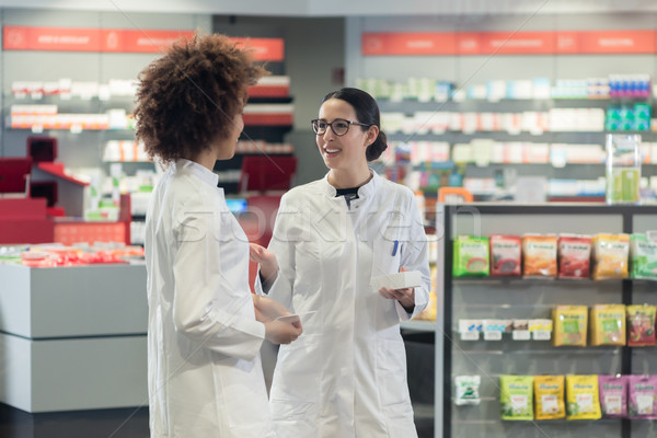 Two friendly colleagues talking while working together as pharmacists Stock photo © Kzenon