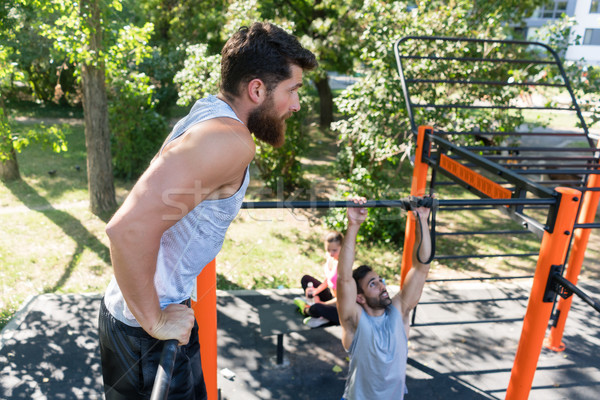 Two muscular young men doing bodyweight exercises in a modern outdoor fitness Stock photo © Kzenon