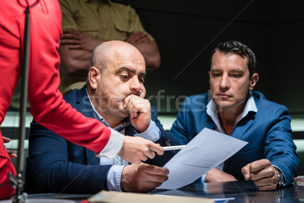 Middle-aged man calling his attorney during a difficult police interrogation Stock photo © Kzenon