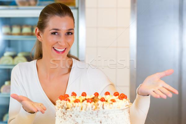 Female baker or pastry chef with torte Stock photo © Kzenon