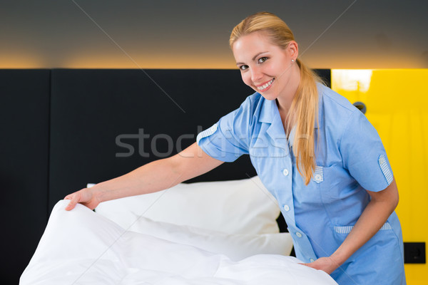Service in the hotel, put clean sheets on bed Stock photo © Kzenon