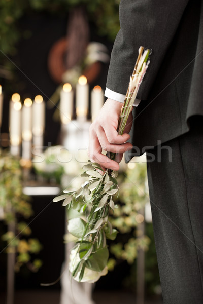 Grief - man with white roses at urn funeral Stock photo © Kzenon