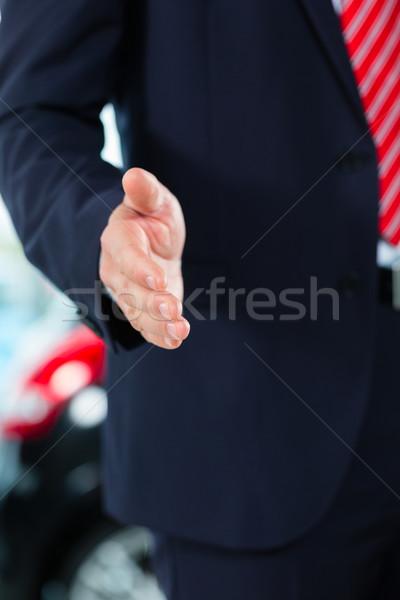 Young man or auto dealer in car dealership Stock photo © Kzenon