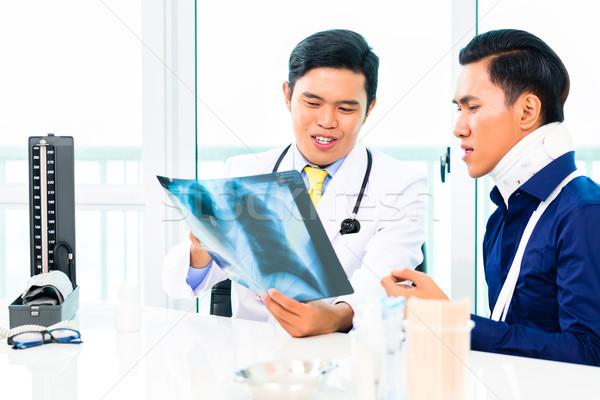 Asian doctor showing X-ray photography Stock photo © Kzenon