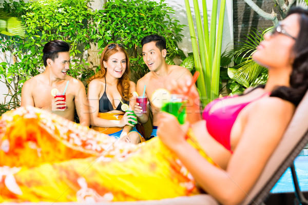 Asian friends partying at pool party in resort Stock photo © Kzenon