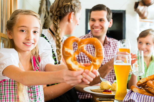 Bavarian girl with family in restaurant Stock photo © Kzenon
