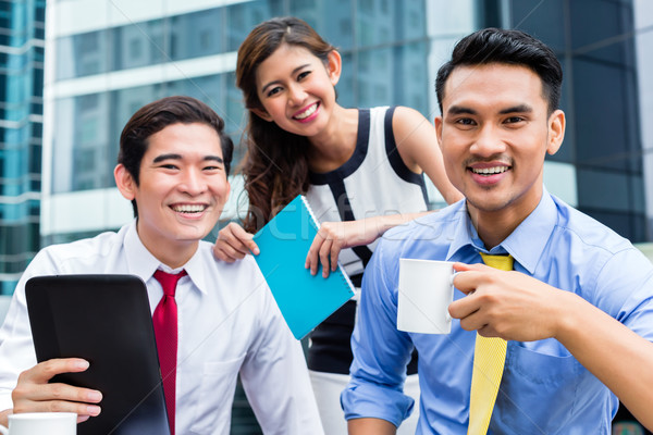 Stock photo: Asian businesspeople working outside with coffee