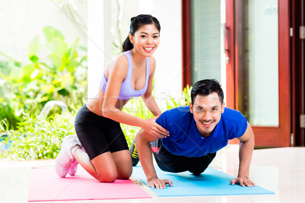 Asian woman helping man with push-up Stock photo © Kzenon