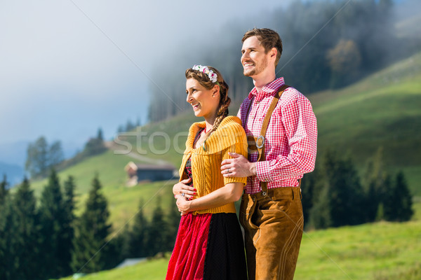 Couple in Tracht on Alp mountain summit at vacation Stock photo © Kzenon