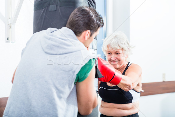 Senior woman with trainer in boxing sparring Stock photo © Kzenon