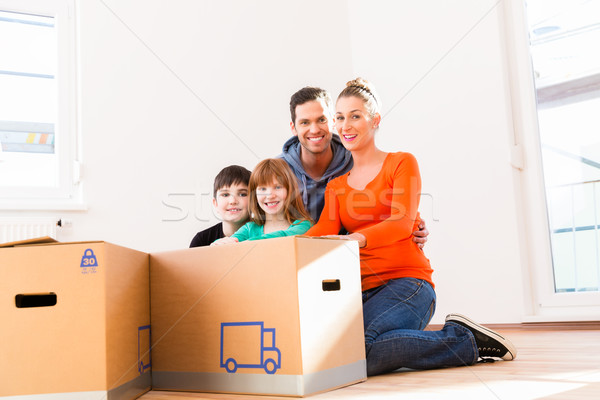 Family unpacking moving boxes in new home Stock photo © Kzenon