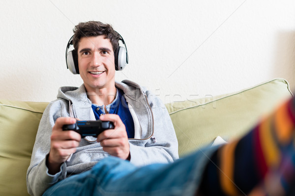 Happy young man playing a video game on console at home Stock photo © Kzenon