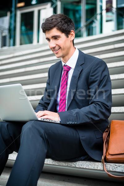 Genç işadamı dizüstü bilgisayar kullanıyorsanız oturma aşağı açık havada Stok fotoğraf © Kzenon