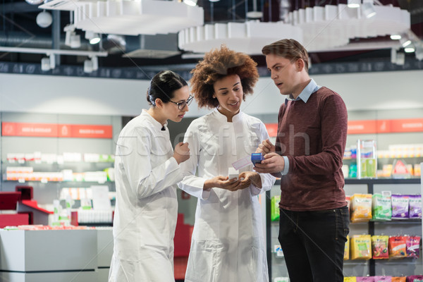 Young man asking for opinion from pharmacists regarding prescrib Stock photo © Kzenon