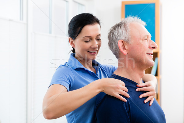 Physio giving shoulder massage to patient Stock photo © Kzenon