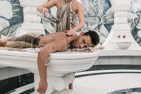 Relaxed man lying down on hot marble bed during traditional Turk Stock photo © Kzenon