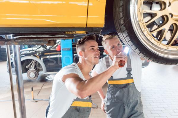 Two dedicated auto mechanics tuning a car through the modificati Stock photo © Kzenon