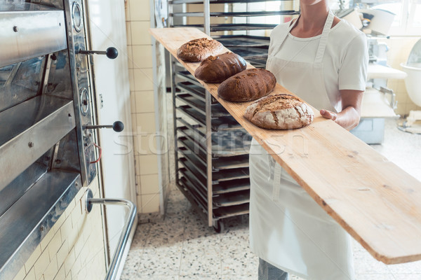 Baker woman presenting bread on board in bakery Stock photo © Kzenon