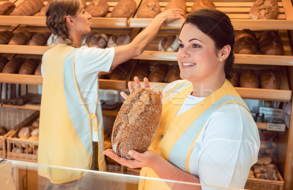 Two salesladies selling bread and other products in bakery shop Stock photo © Kzenon
