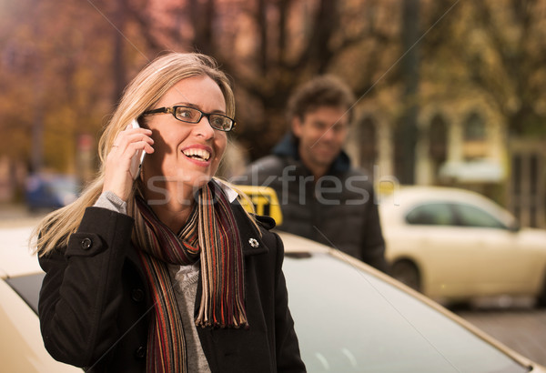 Young woman in front of taxi with phone Stock photo © Kzenon