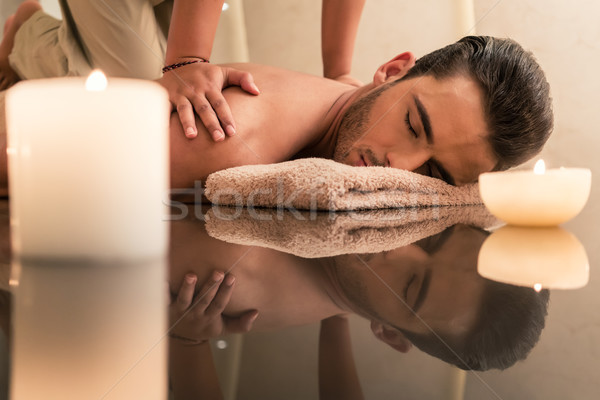 Young man enjoying the healing benefits of traditional Thai massage Stock photo © Kzenon