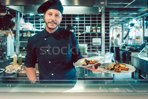 Portrait of a confident master chef holding two plates with tasty food Stock photo © Kzenon