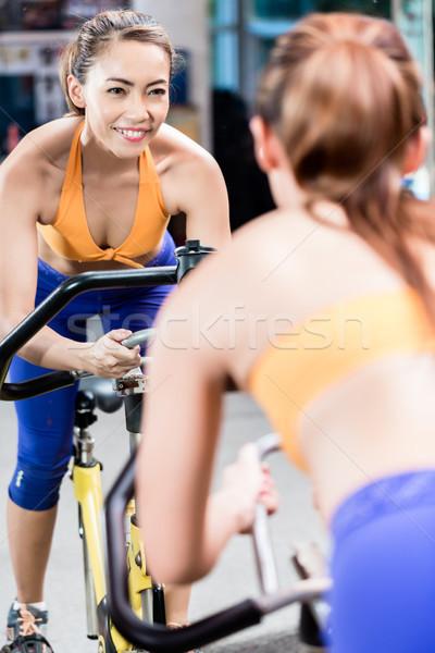 Jovem mulher ginásio ciclismo assistindo Foto stock © Kzenon
