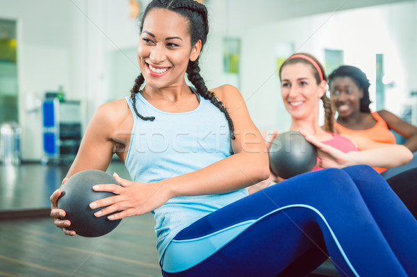 Beautiful woman exercising Russian twist with med ball for strong abs Stock photo © Kzenon